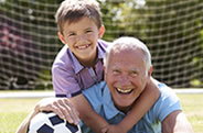 Old man playing soccer with young boy